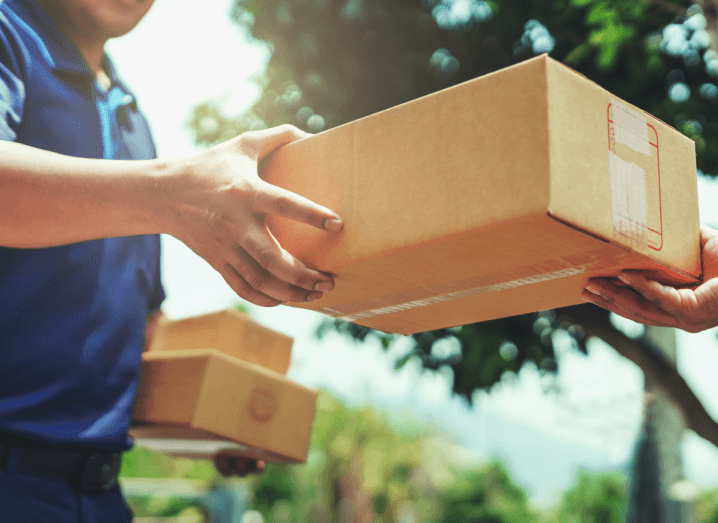 A courier passing a box to a person at their doorstep.
