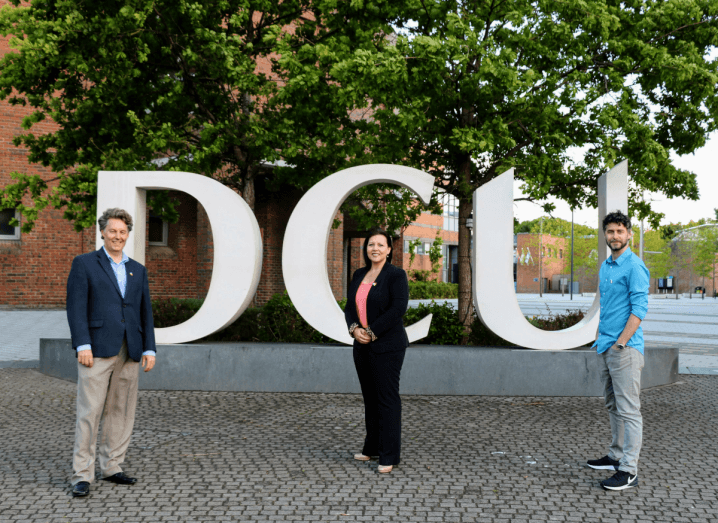 Three people, two men and a woman, standing in front of large letters spelling out DCU on the university's campus.