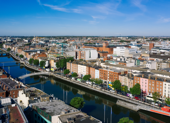 An aerial view of the Liffey river in Dublin, under a blue sky with buildings surrounding it.