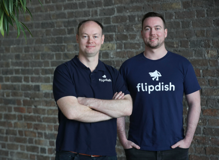 Two men in navy T-shirts with the Flipdish logo stand in front of a brick wall.
