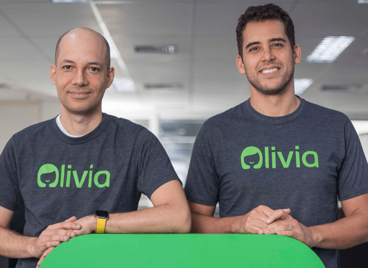 A man with a shaved head and a man with brown hair stand beside each other with their hands on a green surface. They are both wearing grey T-shirts with the logo for Olivia.