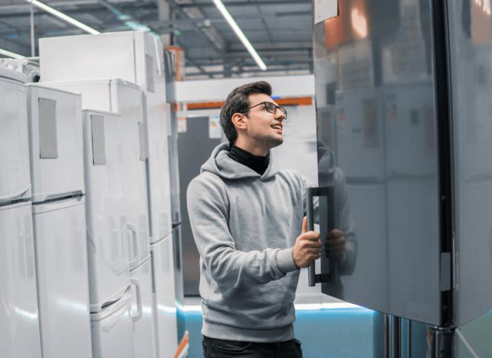 A man looking in a fridge in an appliance store.