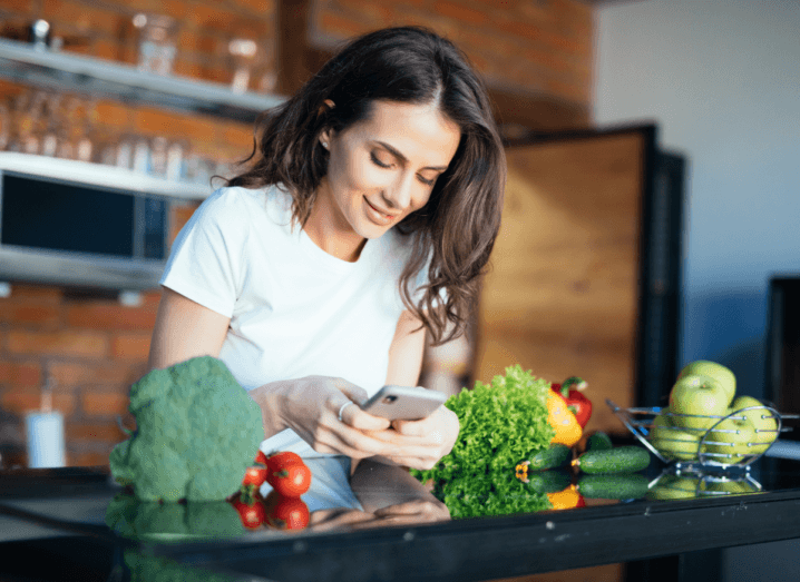 A woman in a white T-shirt, with long brown hair, using a phone in a kitchen in front of a counter, which is covered in vegetables.