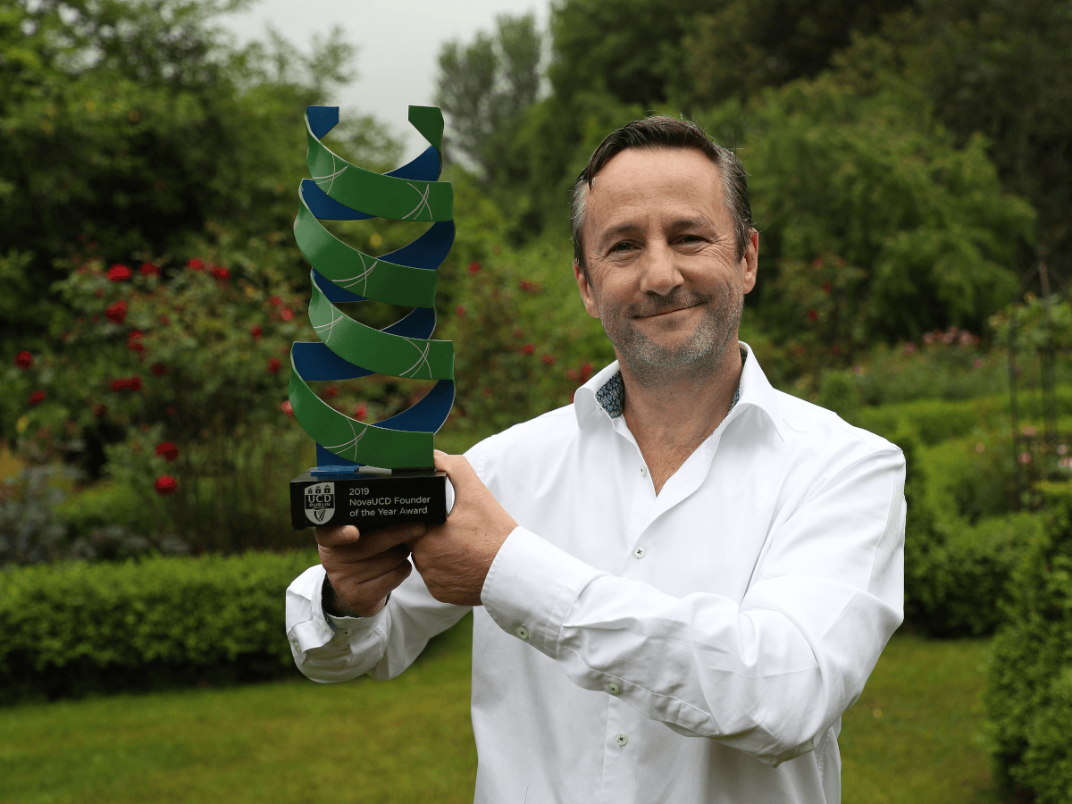 A man with brown hair and grey stubble stands in a large garden holding an award. He is wearing a white shirt.