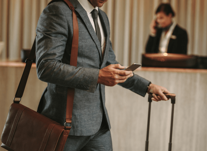 A man in a grey suit wearing a brown leather satchel over his shoulder looks at his mobile phone while wheeling a suitcase in a hotel lobby.