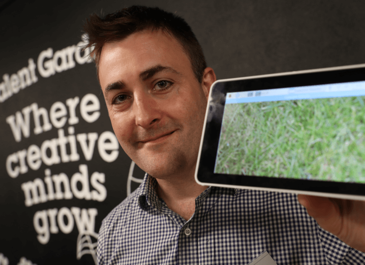 A man with brown hair holding a tablet and standing in front of a wall with the Talent Garden logo on it.