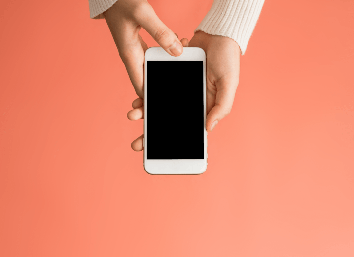 A person holding a smartphone in front of a salmon-pink background.