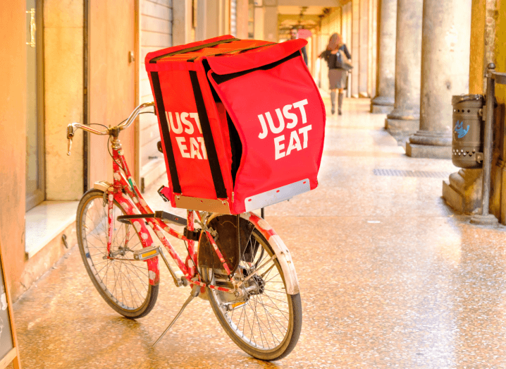 A bike with a Just Eat delivery bag on the back of it.