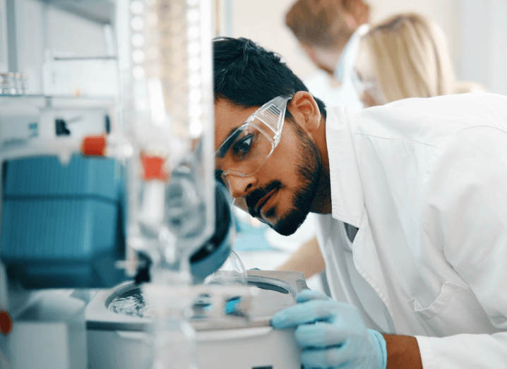 A young man in a lab looking at a piece of equipment. He is wearing goggles and a white coat.