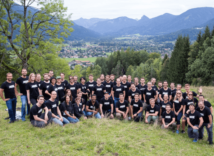 A large group of people standing in grass in front of scenic mountains with a village in the background. The group of people are wearing black t-shirts with the Mapillary company logo on the front.