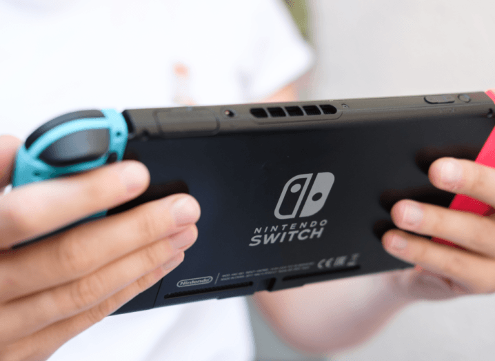 A person in a white T-shirt playing on a Nintendo Switch.