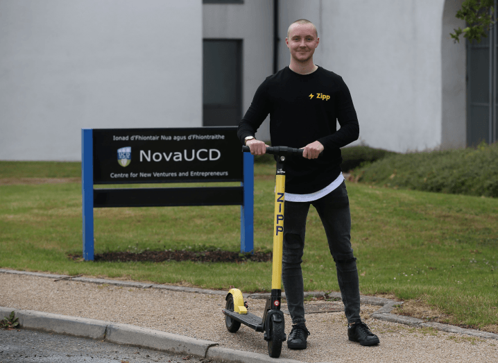A young man wearing a black Zipp Mobility shirt and black jeans stands in front of a NovaUCD sign holding an e-scooter.