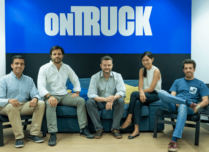 A group of four men sitting on a sofa with a woman. They are sitting in front of a sign that says 'Ontruck'.