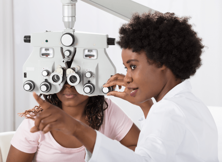 An optometrist testing a patient's eyes. The patient is wearing a pink T-shirt and the optometrist is wearing a white jacket.