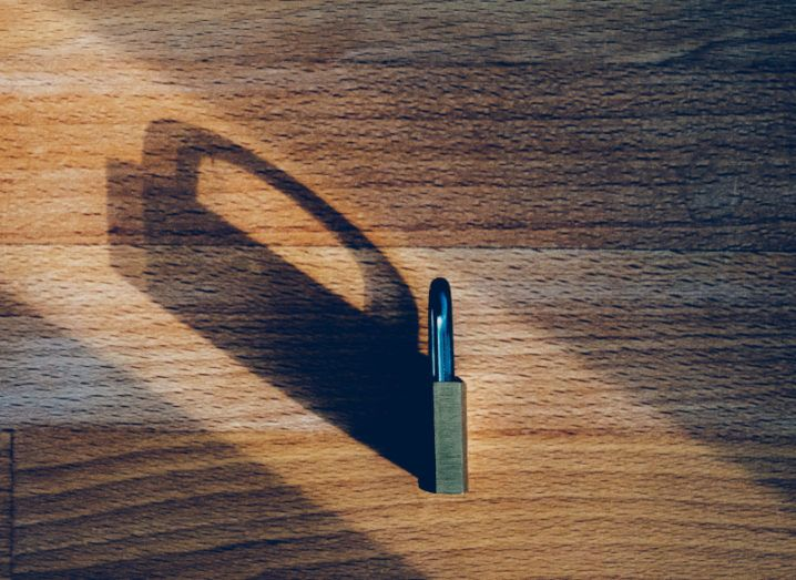 A padlock sits on its side on a wooden table, casting a long shadow.