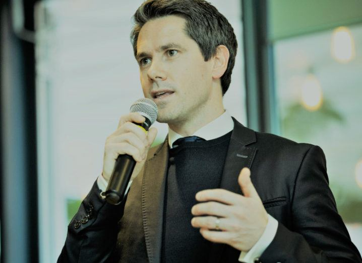 A man in a suit stands on a stage talking into a microphone.