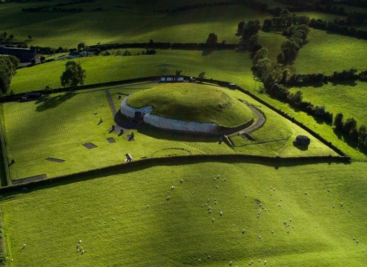 Aerial view of Newgrange, a circular structure covered in grass, blending into the fields around it.