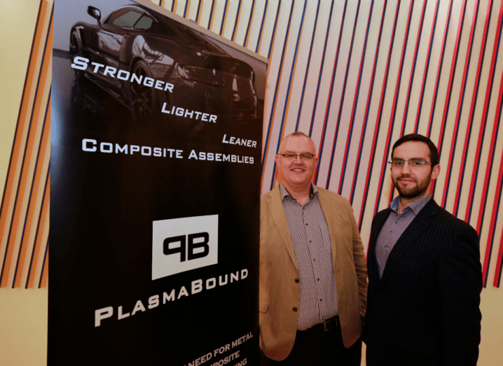 Two men standing beside a black sign that says PlasmaBound and features an image of a car.