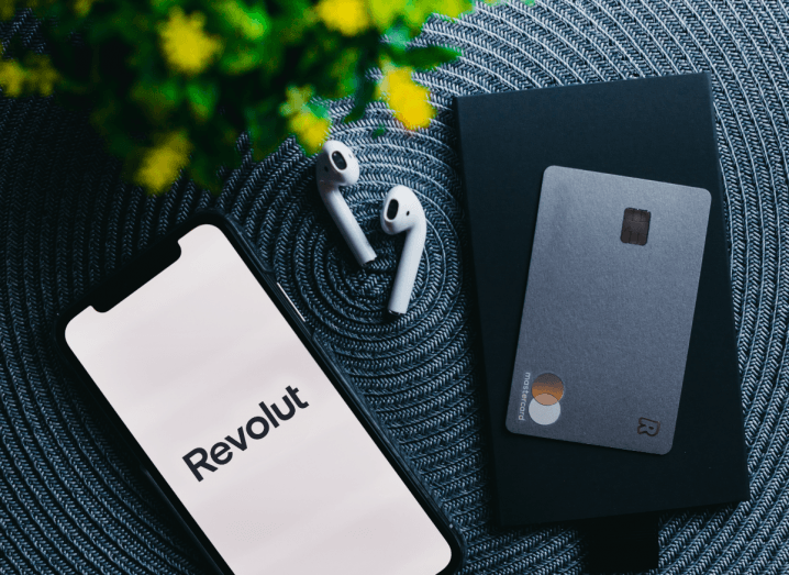 An iPhone on a surface beside a pair of Airpods and a Revolut metal card. The phone's screen displays the Revolut app.