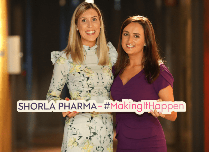 Two women holding a sign that says Shorla Pharma. The woman on the left has blonde hair and the woman on the right has brown hair.