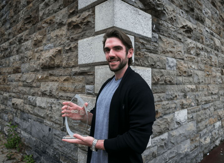 A man with brown hair and a brown beard holds a glass award while standing in front of a grey brick building.