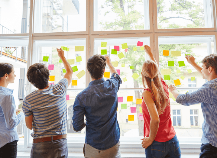 A group of young people sticking post-it notes to a window.