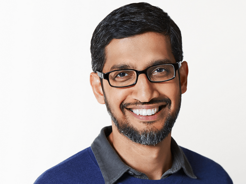 A man with black hair, black rimmed glasses and a black beard with specks of grey in it. He is wearing a grey shirt and navy jumper and standing in front of a white background.