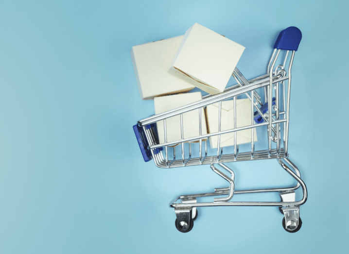 A shopping cart with white boxes in it in front of a blue background.