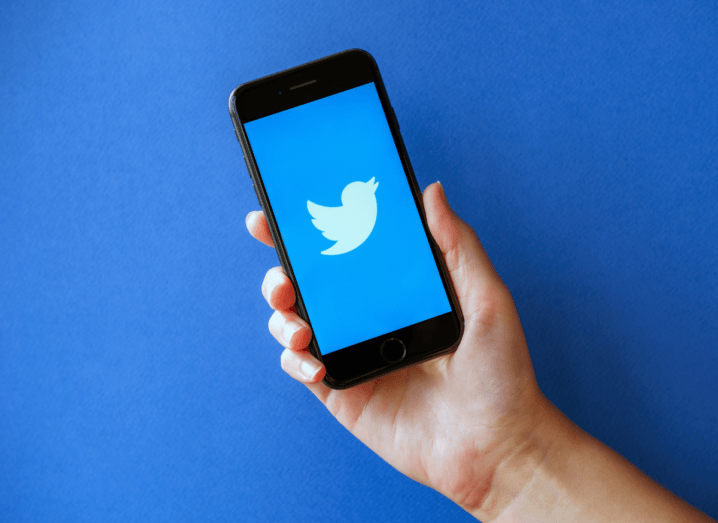 The Twitter logo displayed on a phone, which is held in front of a blue background.