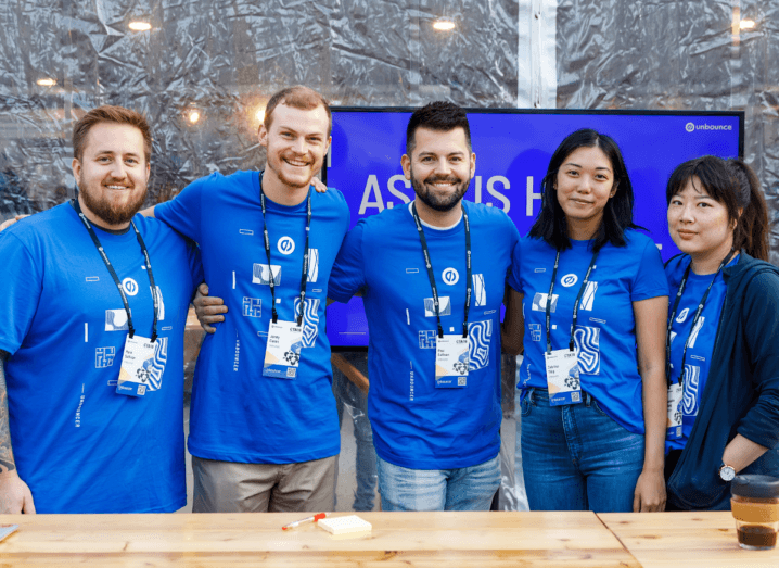 A group of people in blue T-shirts standing in front of a table at what appears to be a trade show.