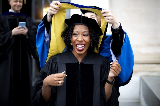 Ciara Sivels smiling while having her PhD graduation stole put on her.