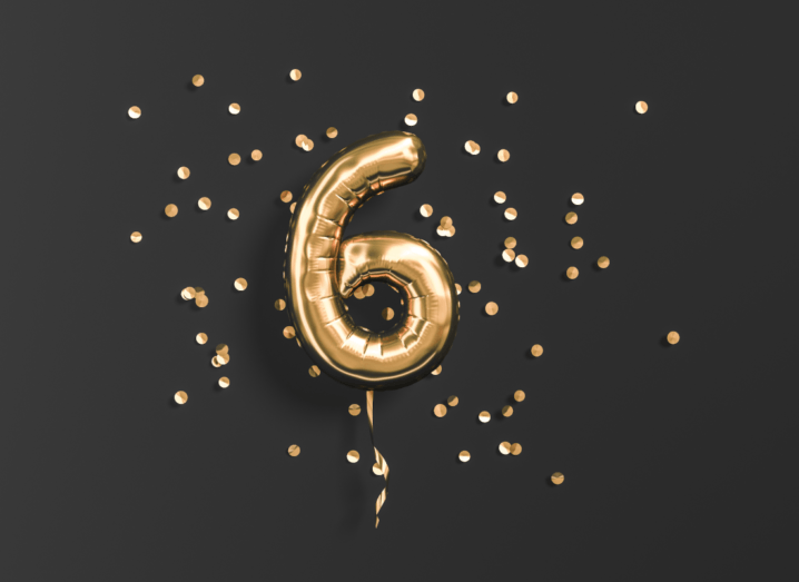 A balloon in the shape of the number six surrounded by gold confetti on a black background.