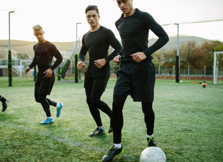 Three football players warming up while wearing all-black sports gear on a football pitch.