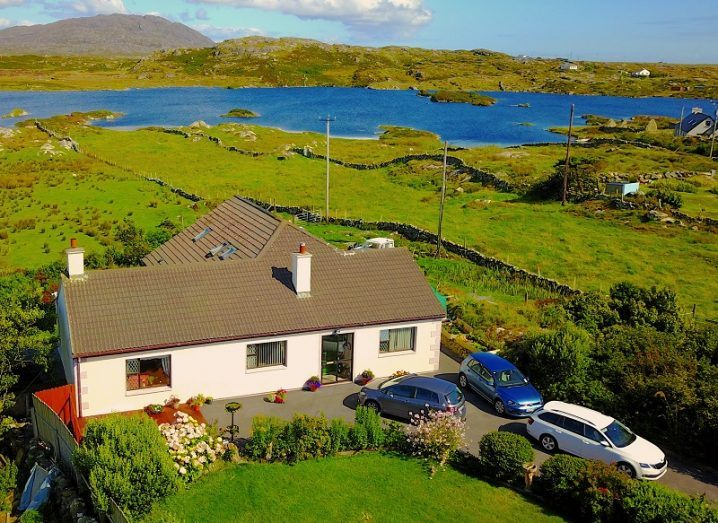Aerial view of a holiday cottage in Ireland with a lake in the background.