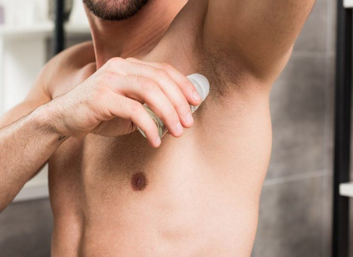 Cropped view of a man applying roll-on deodorant to his armpit.