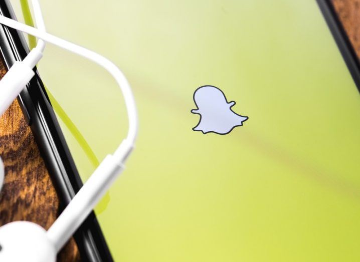 Snapchat logo on a smartphone screen beside a pair of earphones.