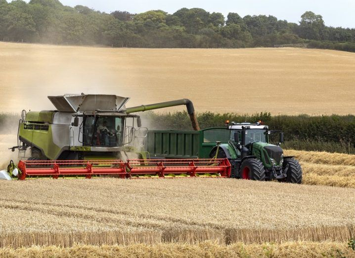 A combine harvester working in a field of wheat beside a tractor.