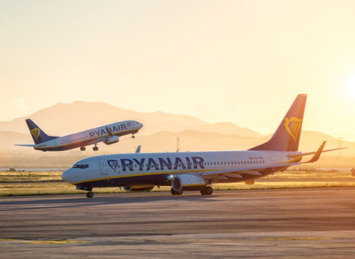 Ryanair planes on the runway at sunset with one in take-off and another taxing to departure.