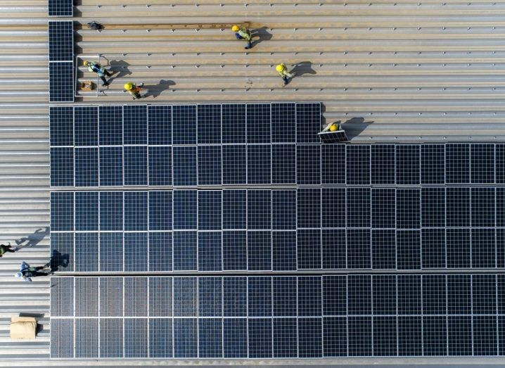 Bird's-eye view of solar panels being installed on a large factory roof.
