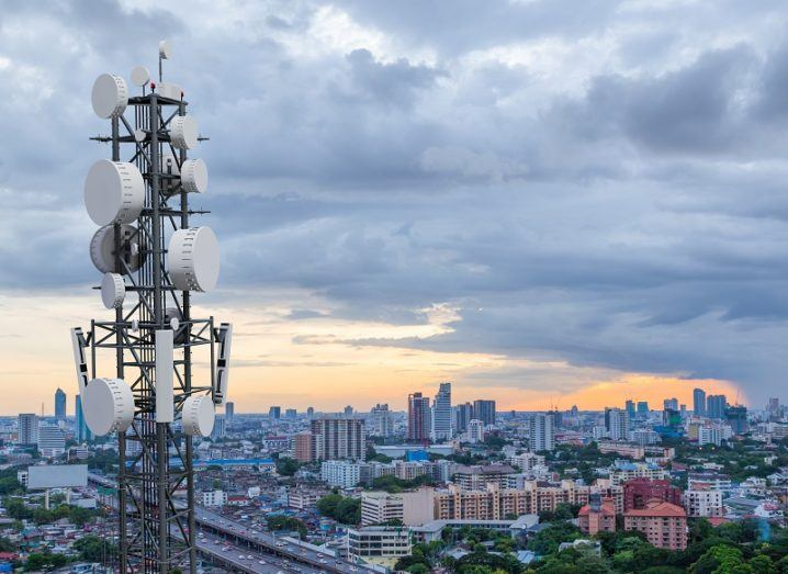 Telecoms tower overlooking a cityscape at dusk.