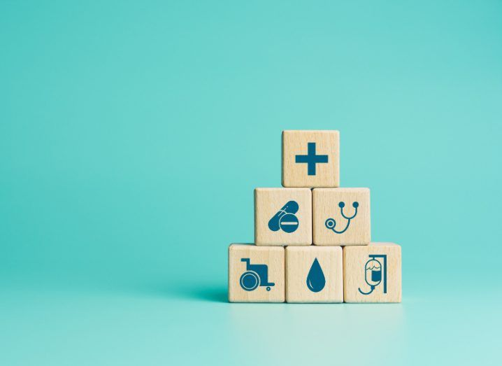 Healthcare concept illustrations on wooden blocks against a turquoise background.