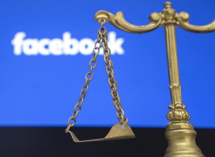 Legal scales in front of a screen with the Facebook logo on it.