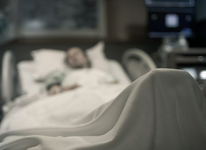 Blurred image of a woman in a hospital bed.