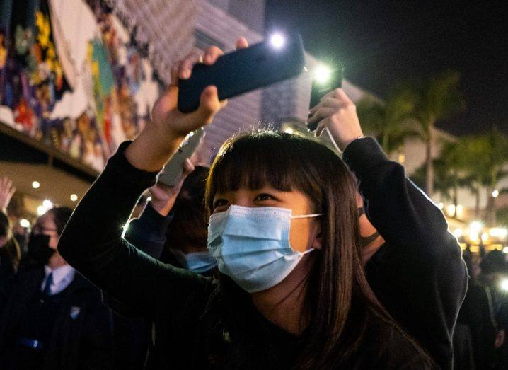 Woman wearing a face mask and holding up a phone with its torch on during a Hong Kong protest.