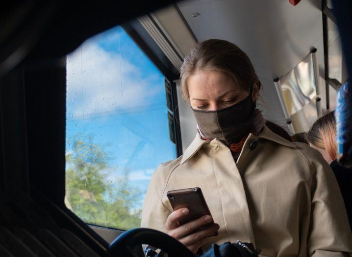 Woman wearing a face mask on public transport while looking at her phone.