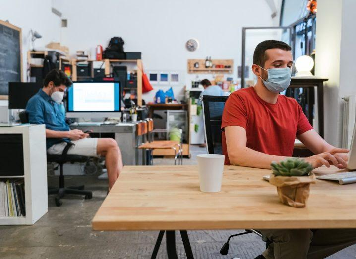 A start-up office with two men wearing face masks at their desks.