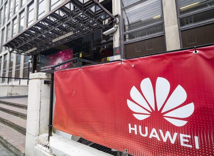 Huawei's logo on a red banner outside an office building.