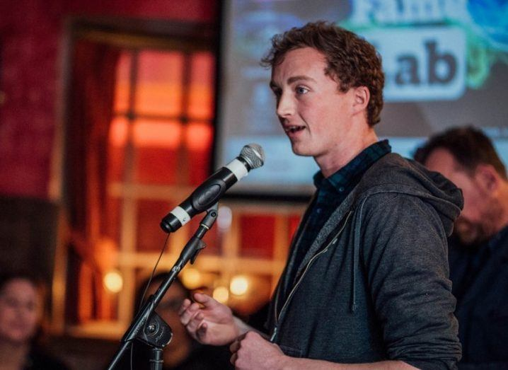 Andrew McGovern talking into a microphone at a FameLab event.