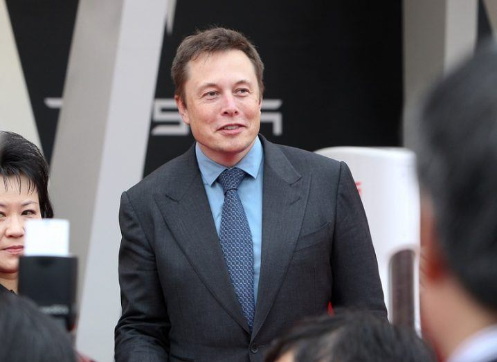 Elon Musk in a dark suit and blue shirt at a Tesla event.