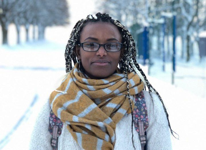 Abeba Birhane wearing a yellow scarf and white jacket against a snowy background.